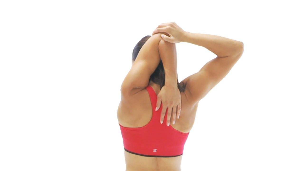 завести согнутую руку за спину через верх
